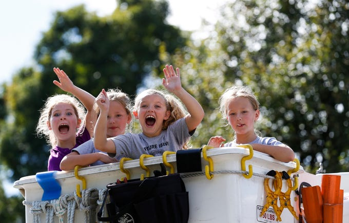 Children throw candy from the back of a bucket truck in the 2018 Labor Day Parade on Monday, Sept. 3, 2018.