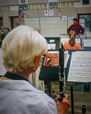 Vero Beach Chamber Orchestra clarinetist Bonnie Myers looks on as conductor Colbert Page Howell gives notes during a recent rehearsal.