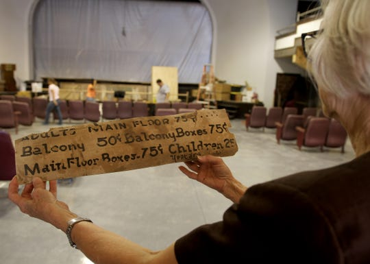 Jannis Hayers, secretary of the Electra Grand Theater Inc. Board, holds an old sign displaying prices for a seat Friday, Aug. 31, 2018, at the Grand Theater in Electra, TX.