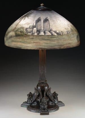 This table lamp with a bronze base and painted glass shade was made by Handel in the early 1900s. It is signed on the base and shade. The shade is 18 inches in diameter, the lamp is 25 inches high. Price, over $5,000.