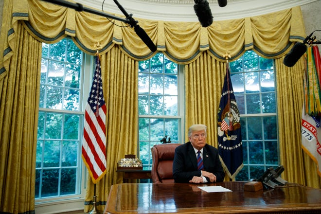 President Donald Trump listens during a phone call with Mexican President Enrique Pena Nieto about a trade agreement between the United States and Mexico, in the Oval Office of the White House.