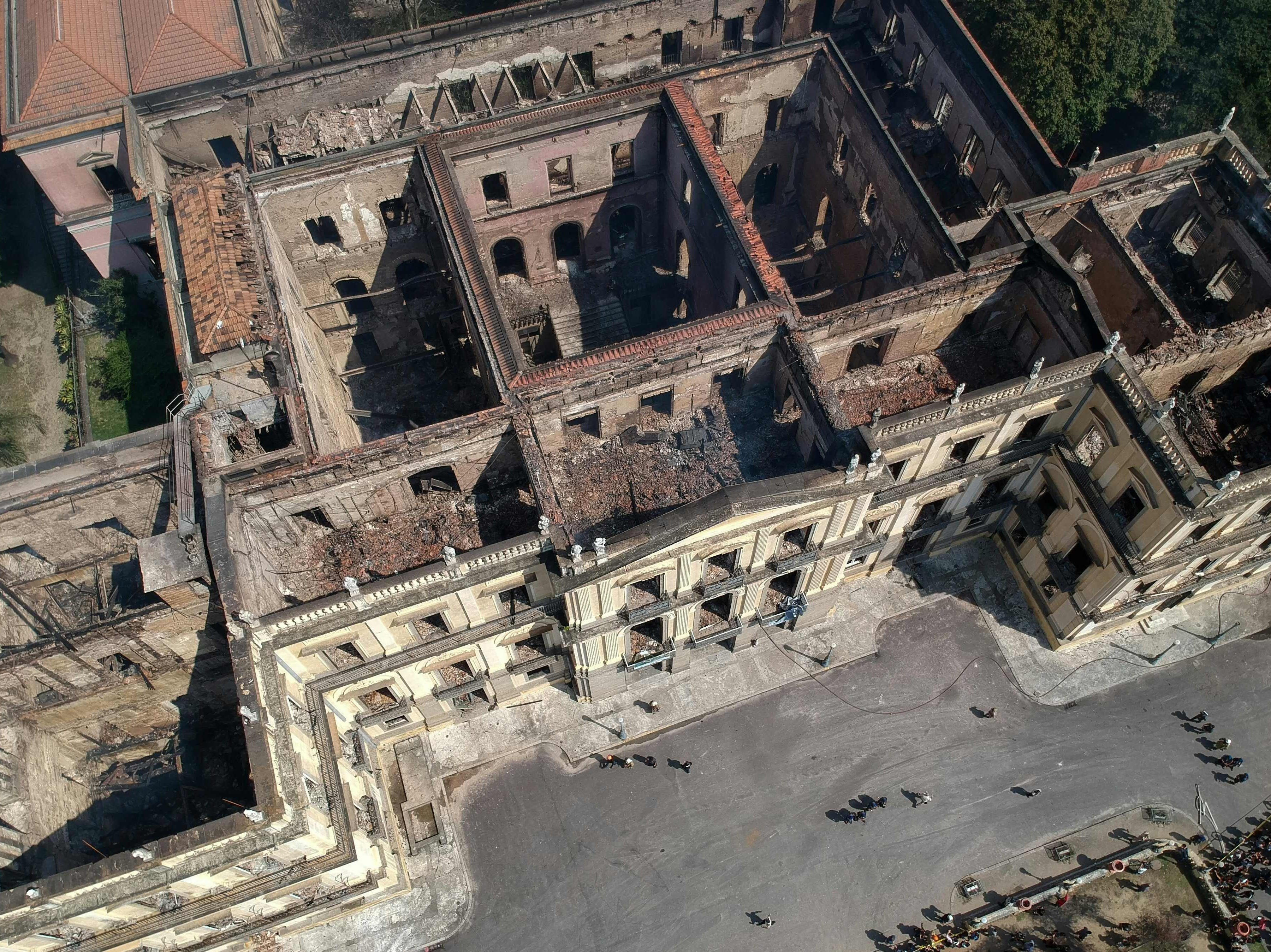 Aerial view of Rio de Janeiro's treasured National Museum, one of Brazil's oldest, on September 3, 2018, a day after a massive fire ripped through the building. - The majestic edifice stood engulfed in flames as plumes of smoke shot into the night sky, while firefighters battled to control the blaze that erupted around 2230 GMT. Five hours later they had managed to smother much of the inferno that had torn through hundreds of rooms, but were still working to extinguish it completely.