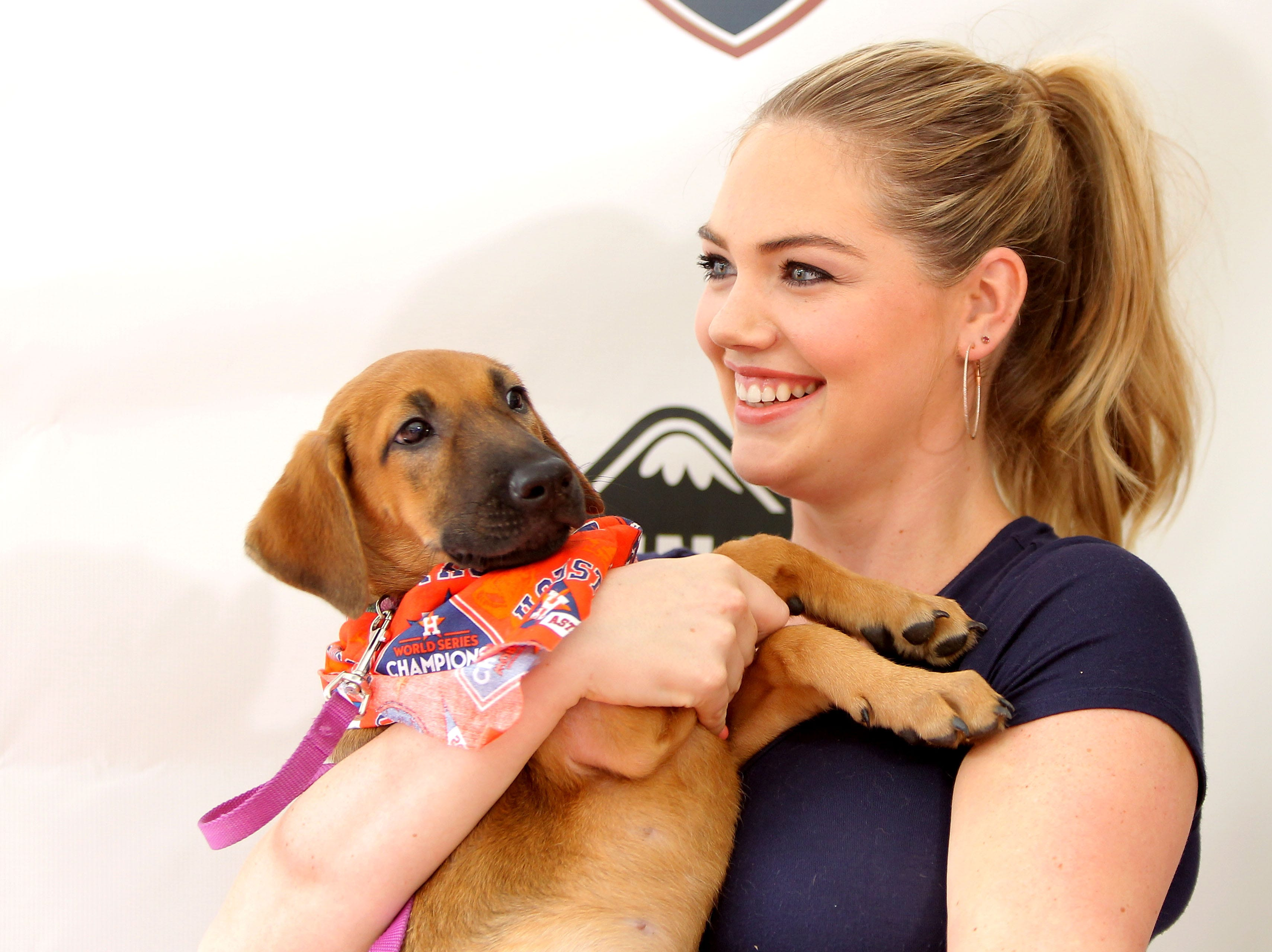 Kate Upton poses for photos with a dog up for adoption during the Astros' Dog Day event.