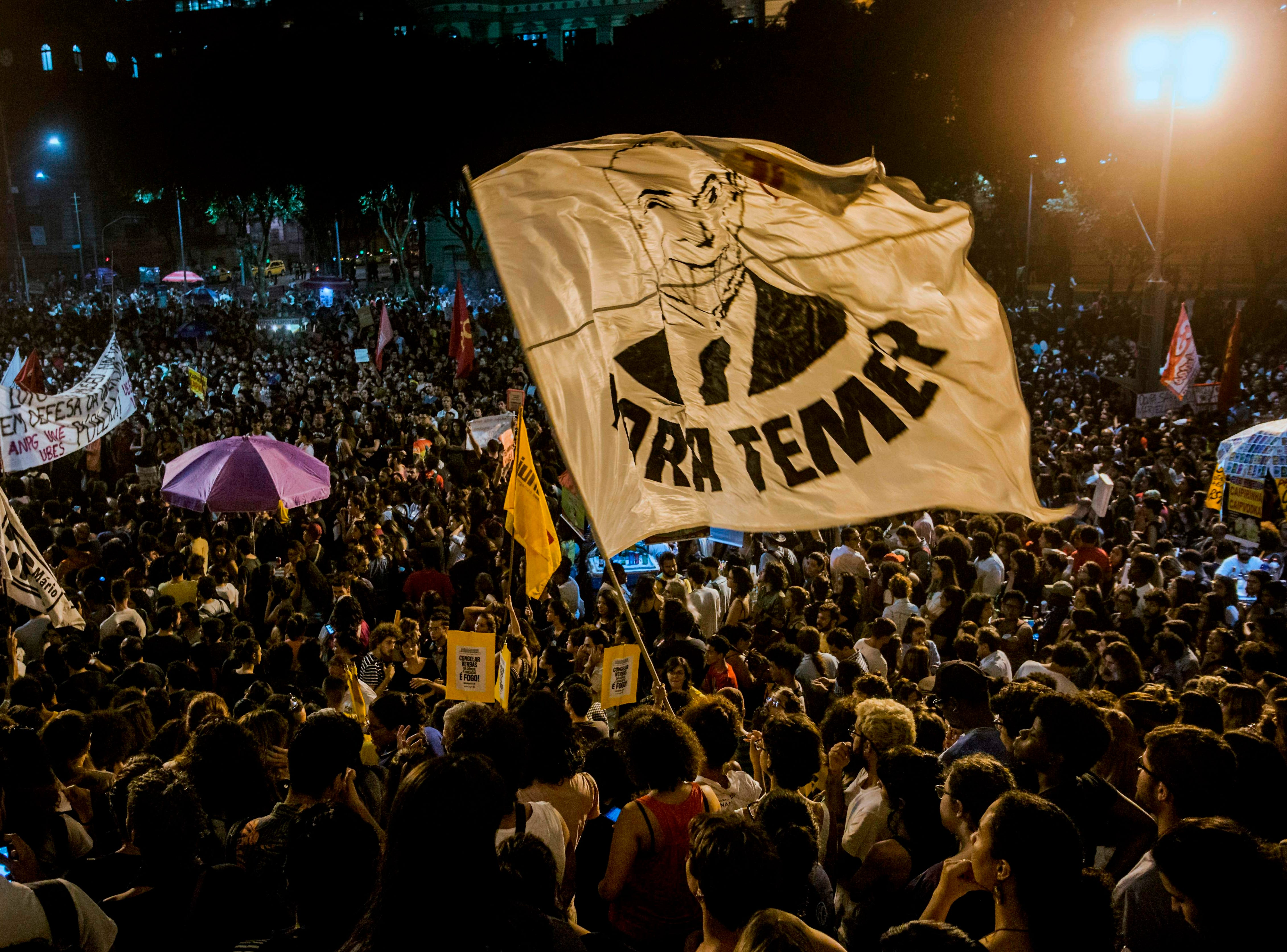 People wave a flag with the image of Brazil's presidente Michel Temer during a protest against the Brazilian government on Sept. 03, 2018, following a massive fire that ripped through Rio de Janeiro's treasured National Museum.