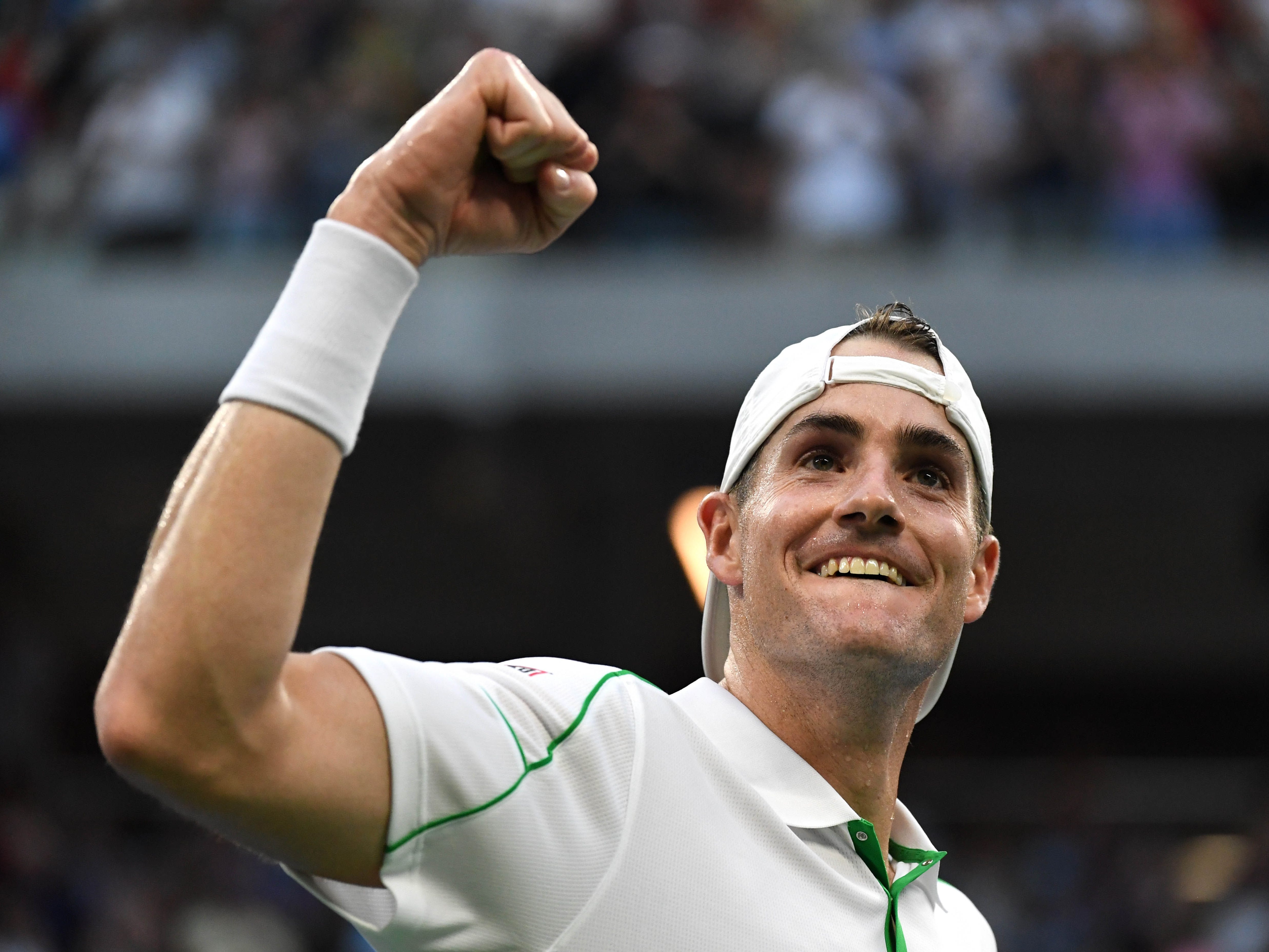 John Isner celebrates after defeating Milos Raonic in the fourth round.