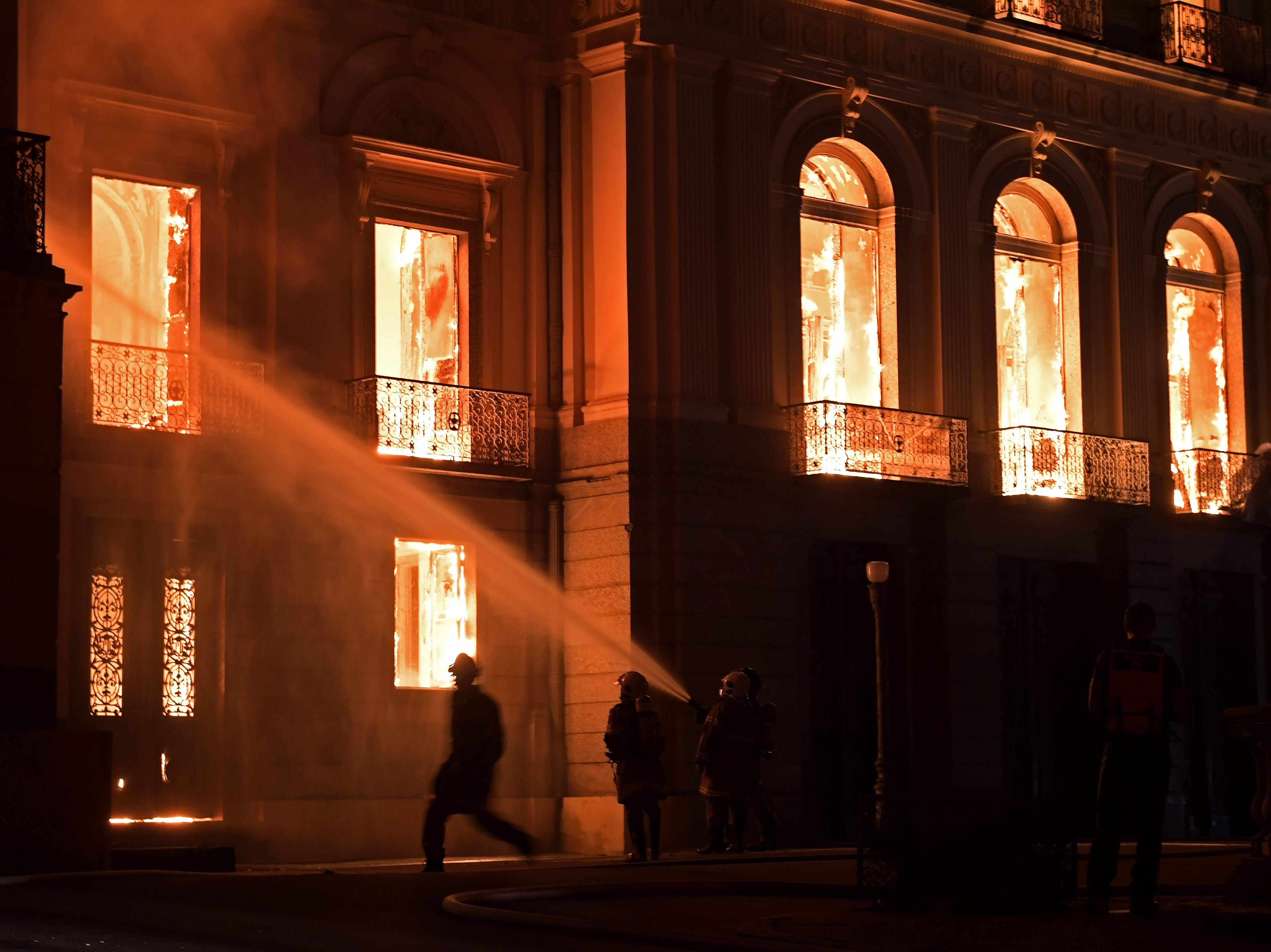 Firefighters work as a massive fire engulfs the National Museum in Rio de Janeiro, one of Brazil's oldest, on September 2, 2018. - The cause of the fire was not yet known, according to local media.