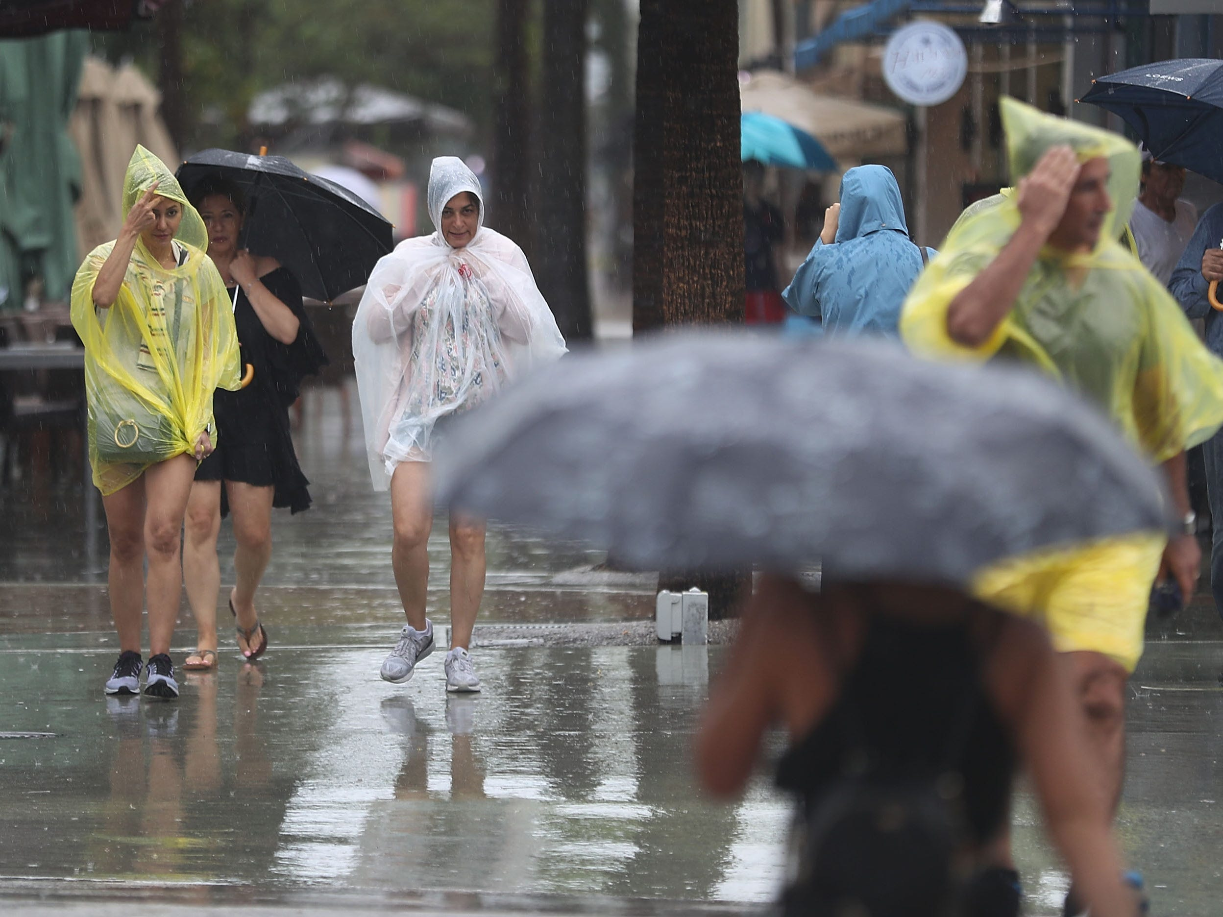 Pedestrians walk through the rain from Tropical Storm Gordon on Sept. 3, 2018, in Miami Beach.