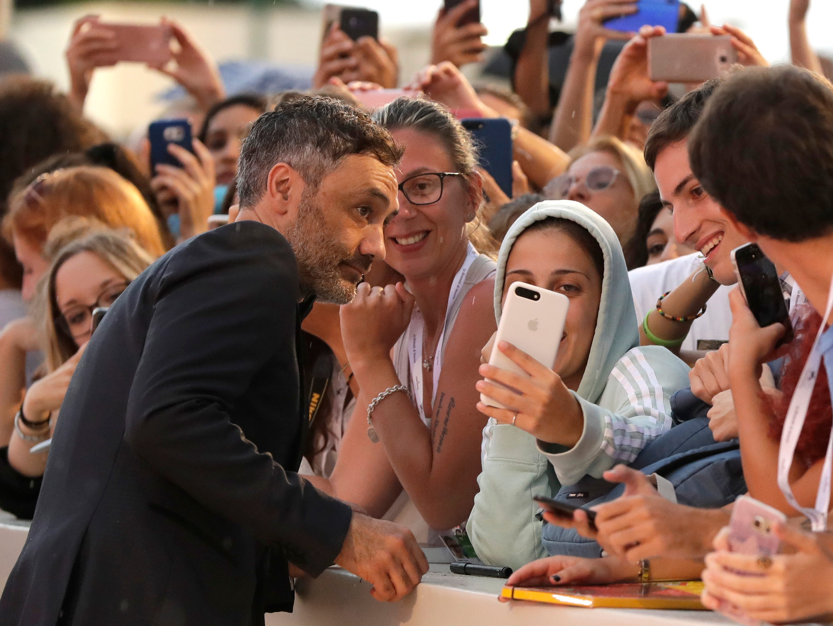 Jury member Taika Waititi poses with fans upon arrival at the premiere of the film 'At Eternity's Gate' at the 75th edition of the Venice Film Festival in Venice, Italy, Monday, Sept. 3, 2018. (AP Photo/Kirsty Wigglesworth) ORG XMIT: LKW139