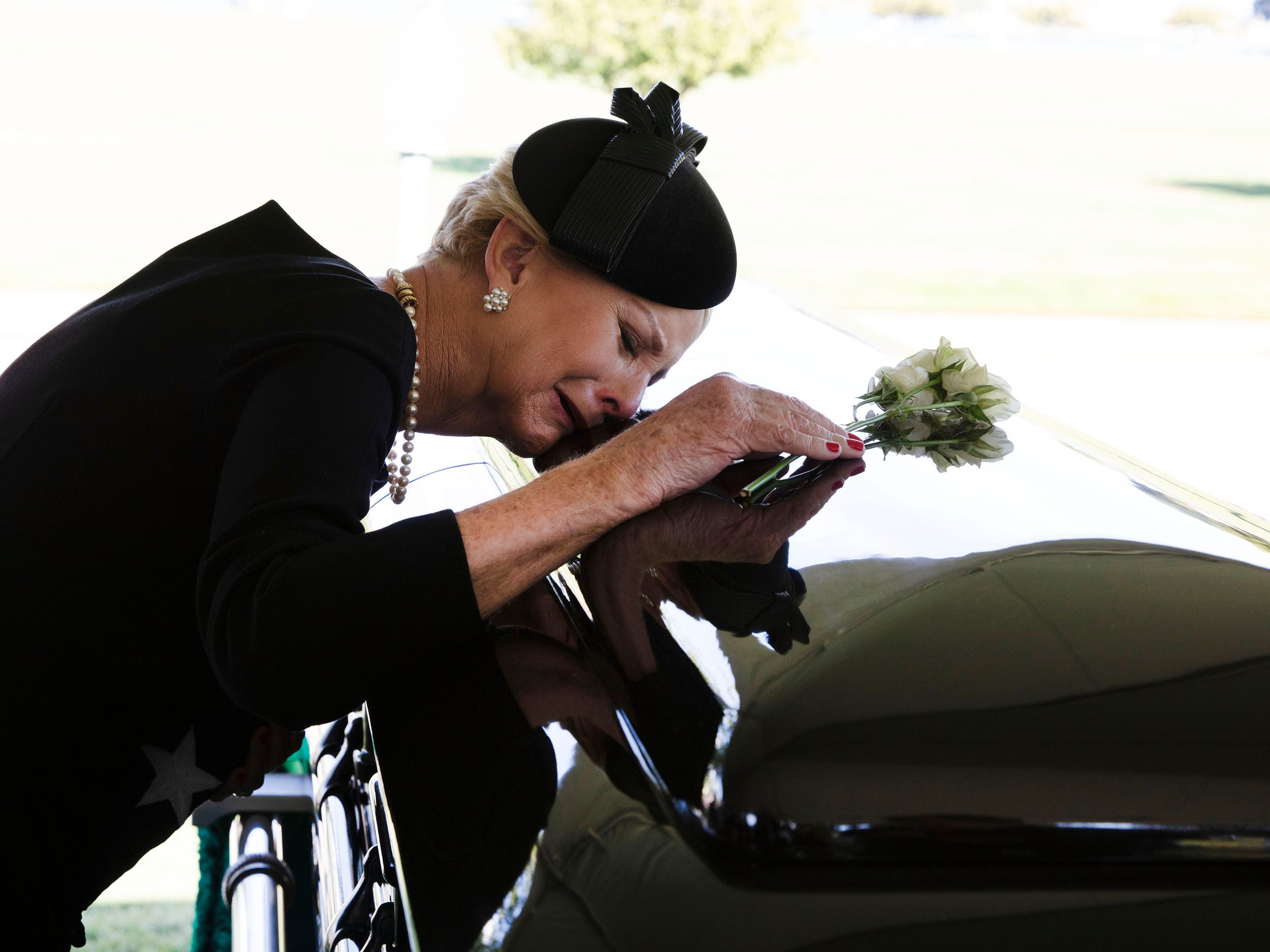 In this photo released by the McCain Family, Cindy McCain lays her head on the casket of her husband Senator John McCain during a burial service at the cemetery at the United States Naval Academy on Sept. 2, 2018, in Annapolis, Md.
