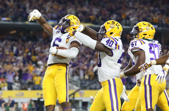 LSU Tigers linebacker Jacob Phillips (6) celebrates a pick-six in the second quarter against the Miami Hurricanes at AT&T Stadium.