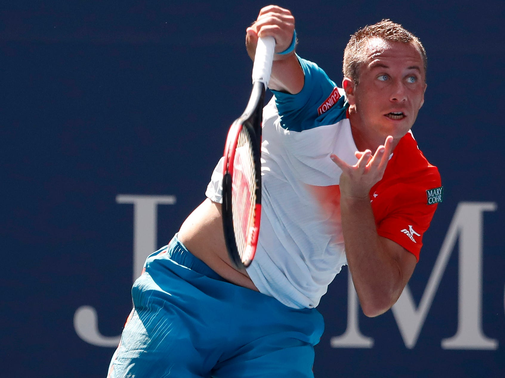 Philipp Kohlschreiber of Germany serves against Kei Nishikori of Japan.