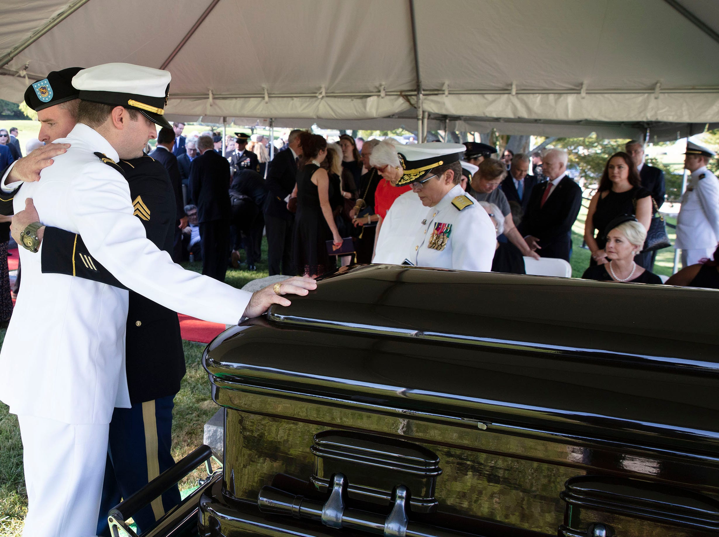 In this photo released by the McCain Family, Jimmy McCain hugs his brother Jack McCain, in white, touching casket, as Cindy McCain, watches during a burial service for Senator John McCain  at the cemetery at the United States Naval Academy on Sept. 2, 2018, in Annapolis, Maryland. A nearly weeklong celebration of the life of US senator John McCain, war hero, maverick, two-time presidential candidate and outspoken critic of Donald Trump, came to a solemn and subdued end on as he was laid to rest at the US Naval Academy in Annapolis, Maryland.