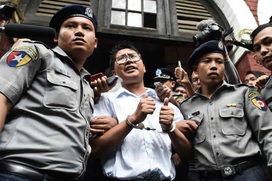 TOPSHOT - Myanmar journalist Wa Lone (C) is escorted by police after being sentenced by a court to jail in Yangon on September 3, 2018. - Two Reuters journalists were jailed on September 3 for seven years for breaching Myanmar's official secrets act during their reporting of the Rohingya crisis, a judge said, a case that has drawn outrage as an attack on media freedom. (Photo by Ye Aung THU / AFP)YE AUNG THU/AFP/Getty Images ORIG FILE ID: AFP_18T361