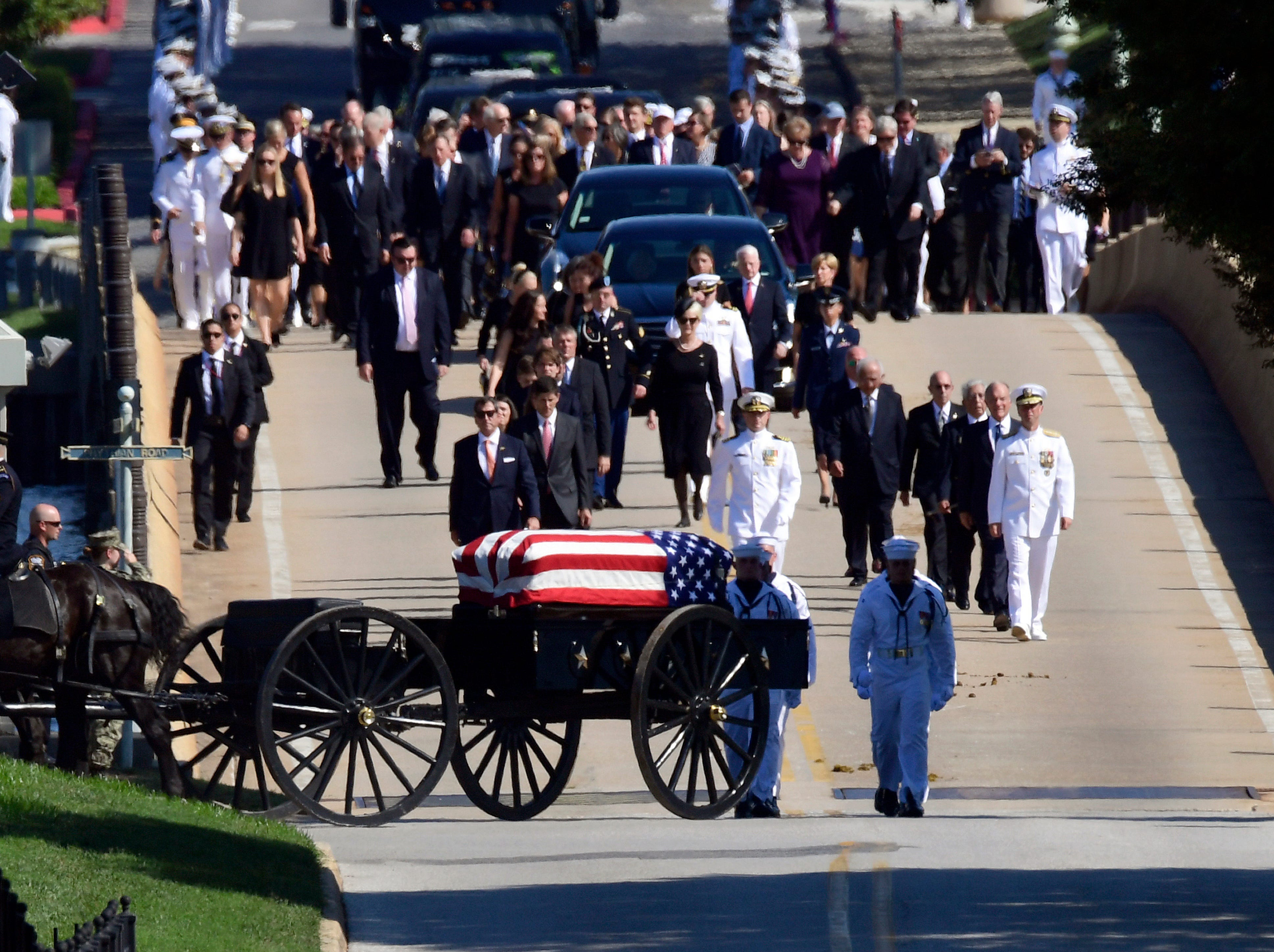 Family members, including Cindy McCain, back center, follow a horse-drawn caisson that carries the casket of Sen. John McCain as it proceeds to the United States Naval Academy cemetery in Annapolis, Md., Sunday, Sept. 2, 2018, for burial. McCain died Aug. 25 from brain cancer at age 81.