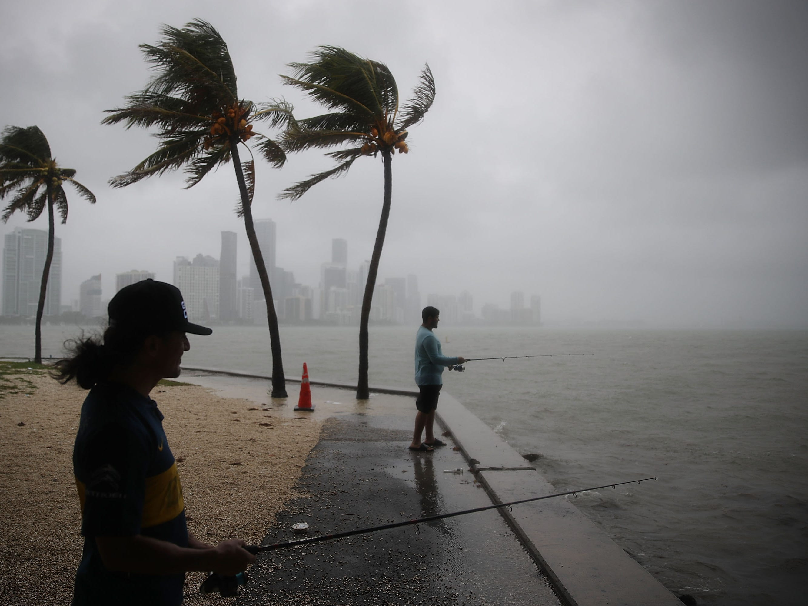 Walter Augier, left, and Jhon M. fish as rain and wind are whipped up by Tropical Storm Gordon on Sept. 3, 2018 in Miami.  Tropical Storm Gordon is heading into the Gulf of Mexico bringing heavy rain and gusty winds to South Florida as it heads for a northern Gulf Coast landfall.