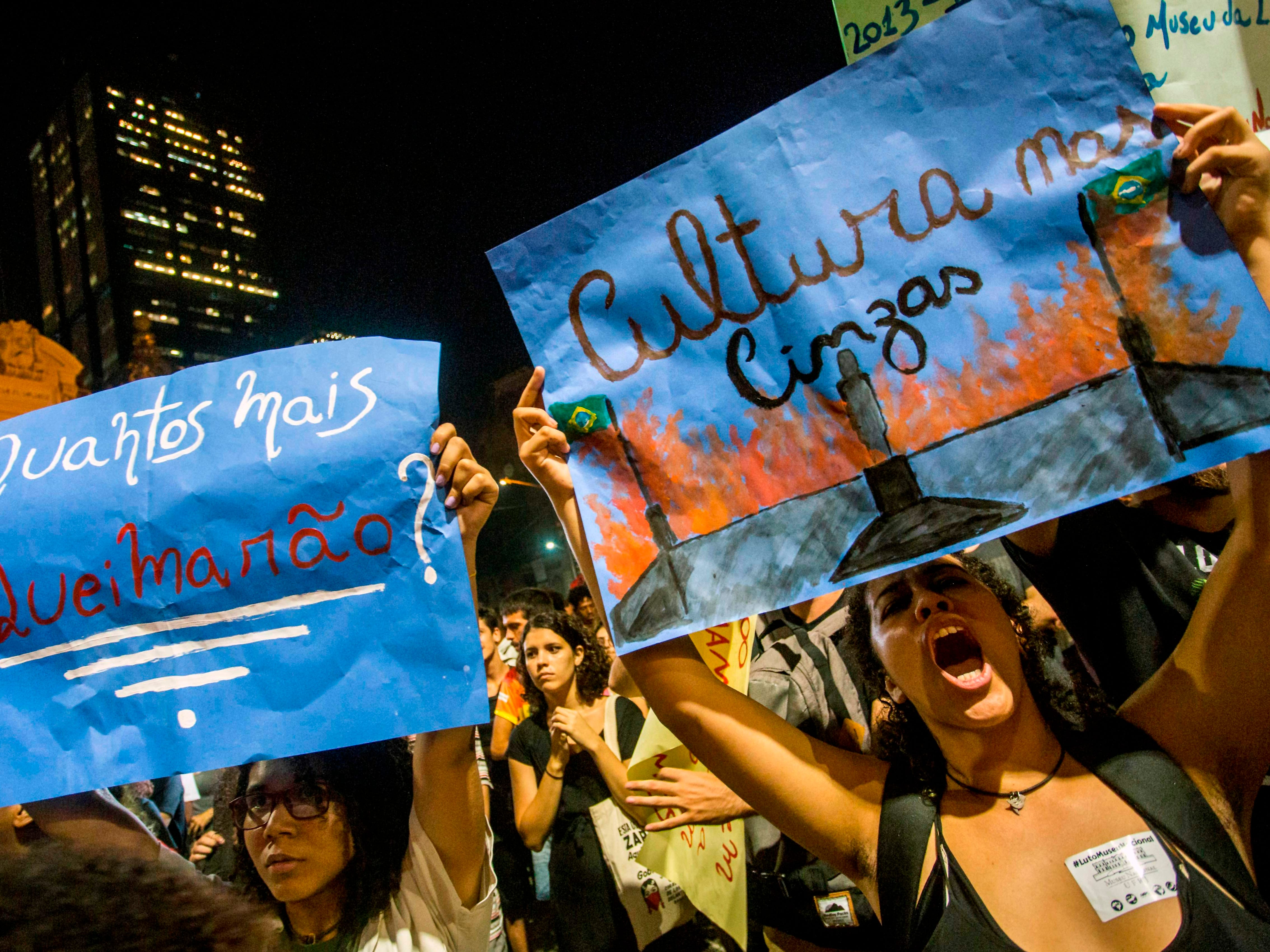 """Women hold signs reading """"How many more will they set on fire"""" (L) and """"Culture on ashes"""" during a protest against the Brazilian government on Sept. 03, 2018, following a massive fire that ripped through Rio de Janeiro's treasured National Museum."""