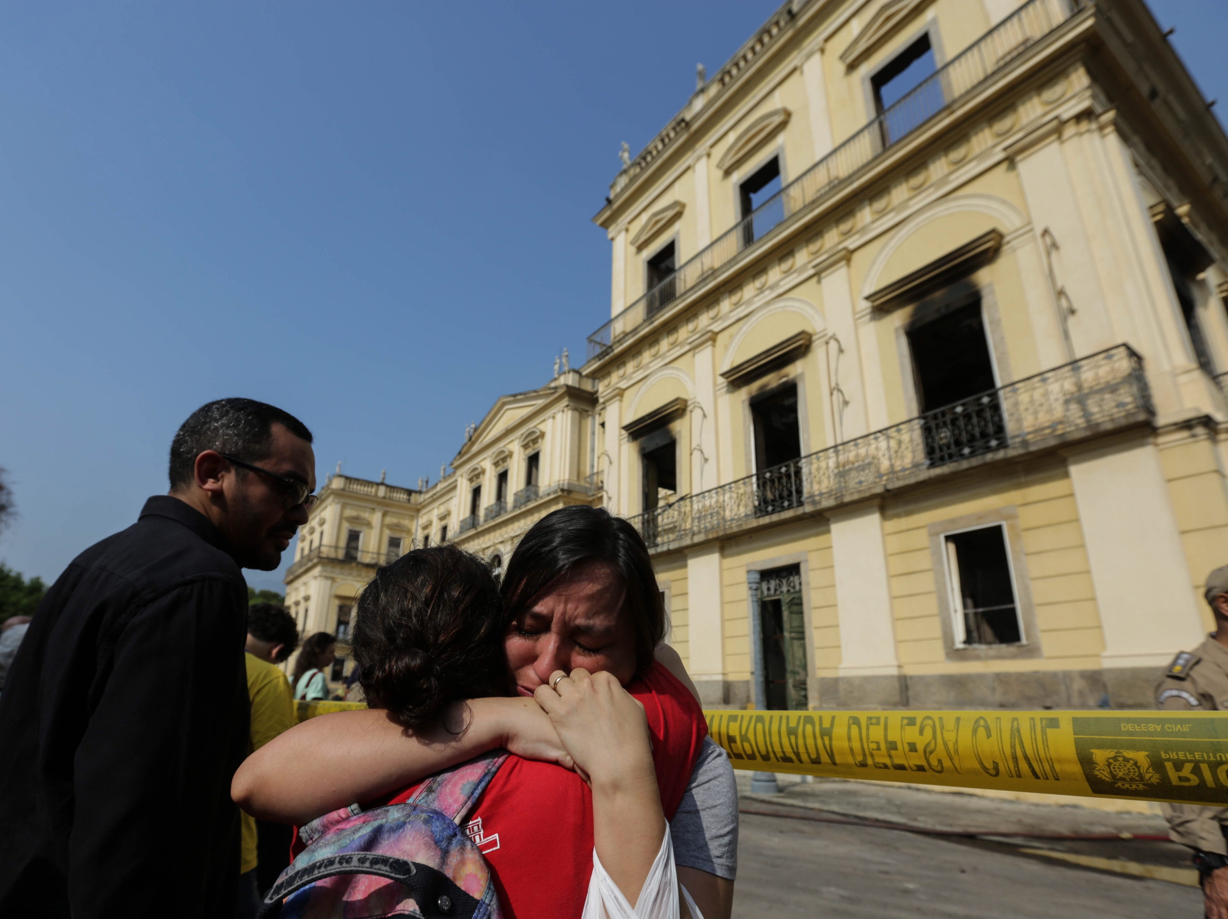 epaselect epa06994608 Civil servants of the National Museum of Rio de Janeiro cry outside the National Museum of Rio de Janeiro, Brazil, 03 September 2018, after after fire destroyed the building on 02 September 2018. The National Museum of Rio de Janeiro, is the oldest in Brazil and  housed some 20 million items, including the skeleton of 'the first American', stuffed animals, mummies and dozens of dinosaur bones.