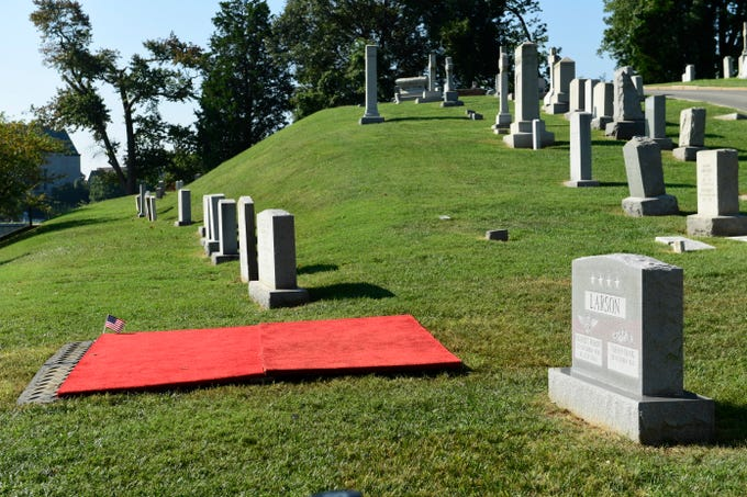 """The covered burial plot for Sen. John McCain sits quietly Monday, Sept. 3, 2018 at the cemetery at the U.S. Naval Academy in Annapolis, Md. Years ago Chuck Larson, whose memorial stone is at right, an admiral himself and an ally throughout McCain's life, reserved four plots at the cemetery, two for McCain and himself, and two for their wives, now widows. Larson died in 2014, and McCain wrote in a recent memoir that he wanted to be buried next to his friend, """"near where it began."""""""