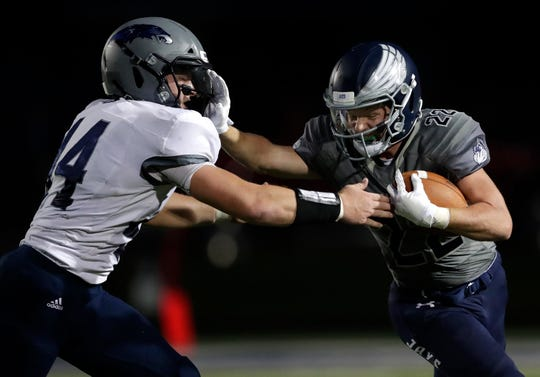 Menasha's Tyler Roehl, right, stiff arms Xavier's Mac Strand during a game at Calder Stadium earlier this season.  Dan Powers/USA TODAY NETWORK-Wisconsin