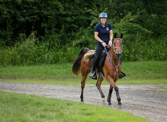 Kelsey Russell, 22, of Williston, Florida, with her horse, Fireman Gold, will compete in the endurance discipline, a 100-mile race, at the FEI World Equestrian Games in Tryon.