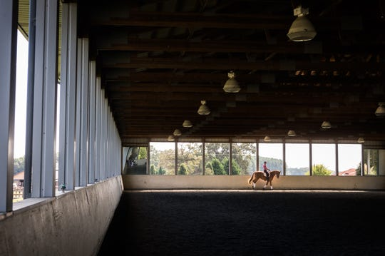 Julio Mendoza rides one of his horses, Heroic Time, at his farm in Columbus.