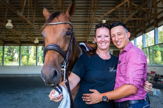 Jess Mendoza and her husband, Julio Mendoza, with one of their horses, Flamenca, at their farm in Columbus.