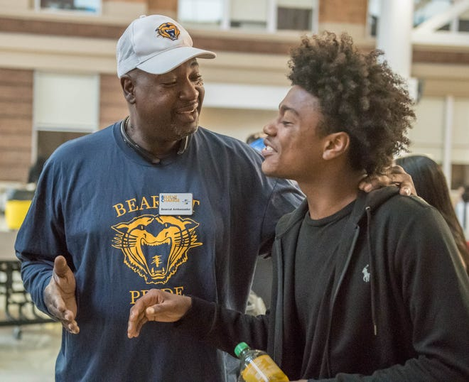 Melvin McKnight, a Bearcat Ambassador, welcomes Battle Creek Central High School junior Drew Santos on the first day of school Tuesday.