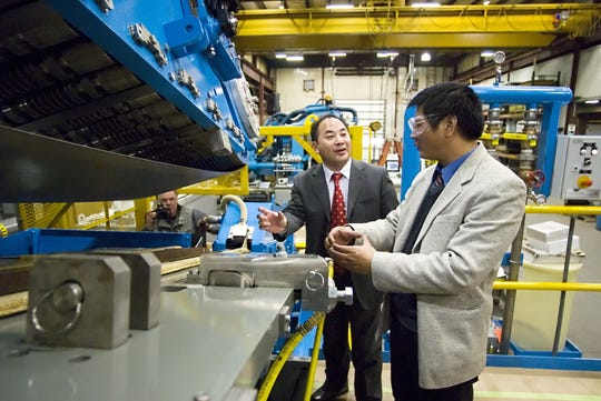 In this file photo, representatives of the Amer Copper Technology Company Ltd. of Tongling China, inspect a machine they'd purchased from Hazelett Corp. in Colchester.