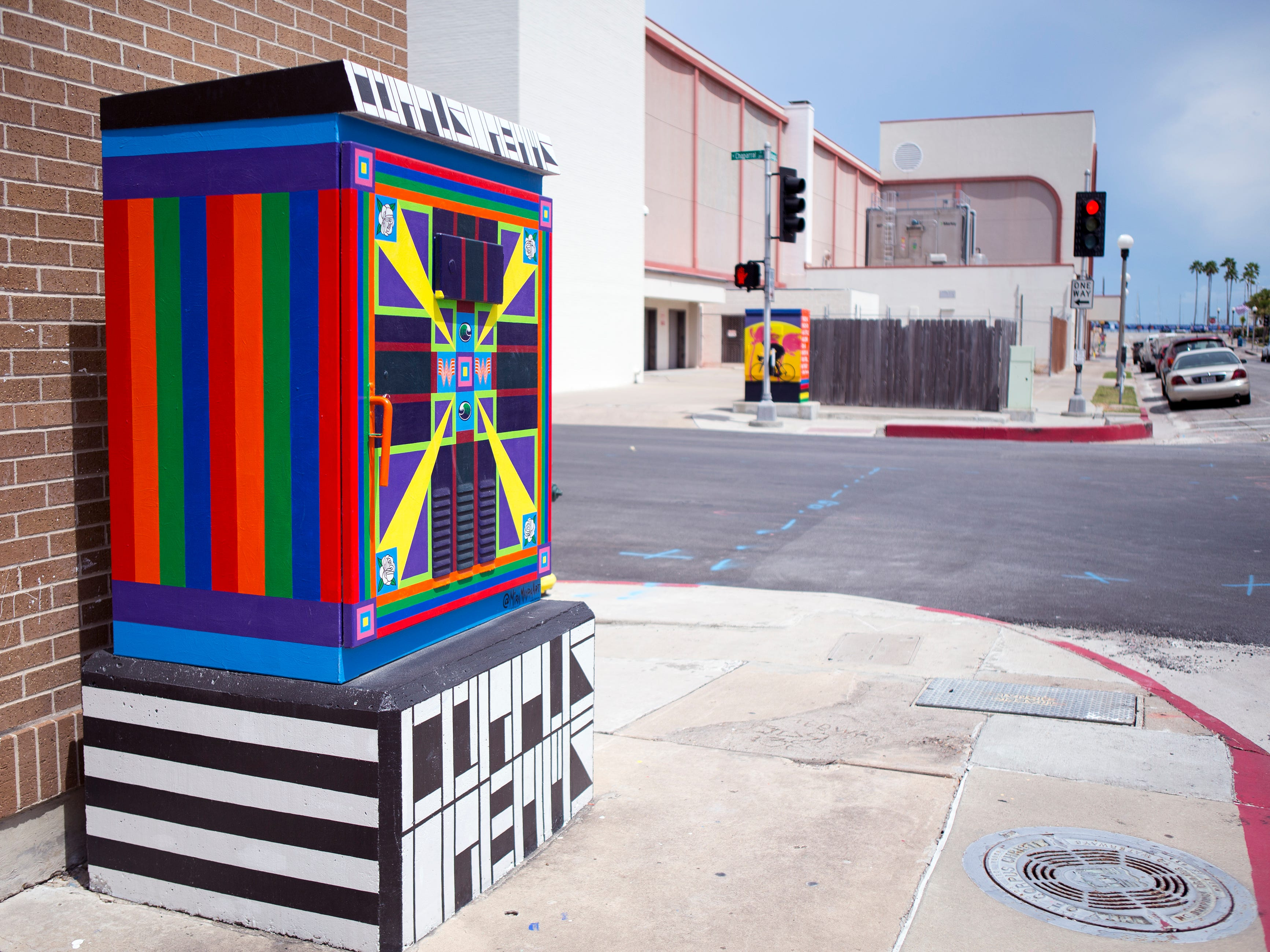 A painted utility box in downtown Corpus Christi is located near the corner of John Sartain and N. Chaparral streets. The Downtown Management District began the process of having the boxes painted in 1997 with a program called Art Sparks. The program allowed students interested in art to paint the boxes over the summer under the supervision of a teacher and get paid for their work. In 2004, the district began using commissioned artists.
