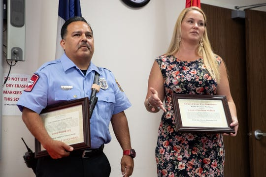 Firefighter II Shawn Gonzales and Heather Orr are presented with awards for helping save a mans life in May at the Corpus Christi International Airport.