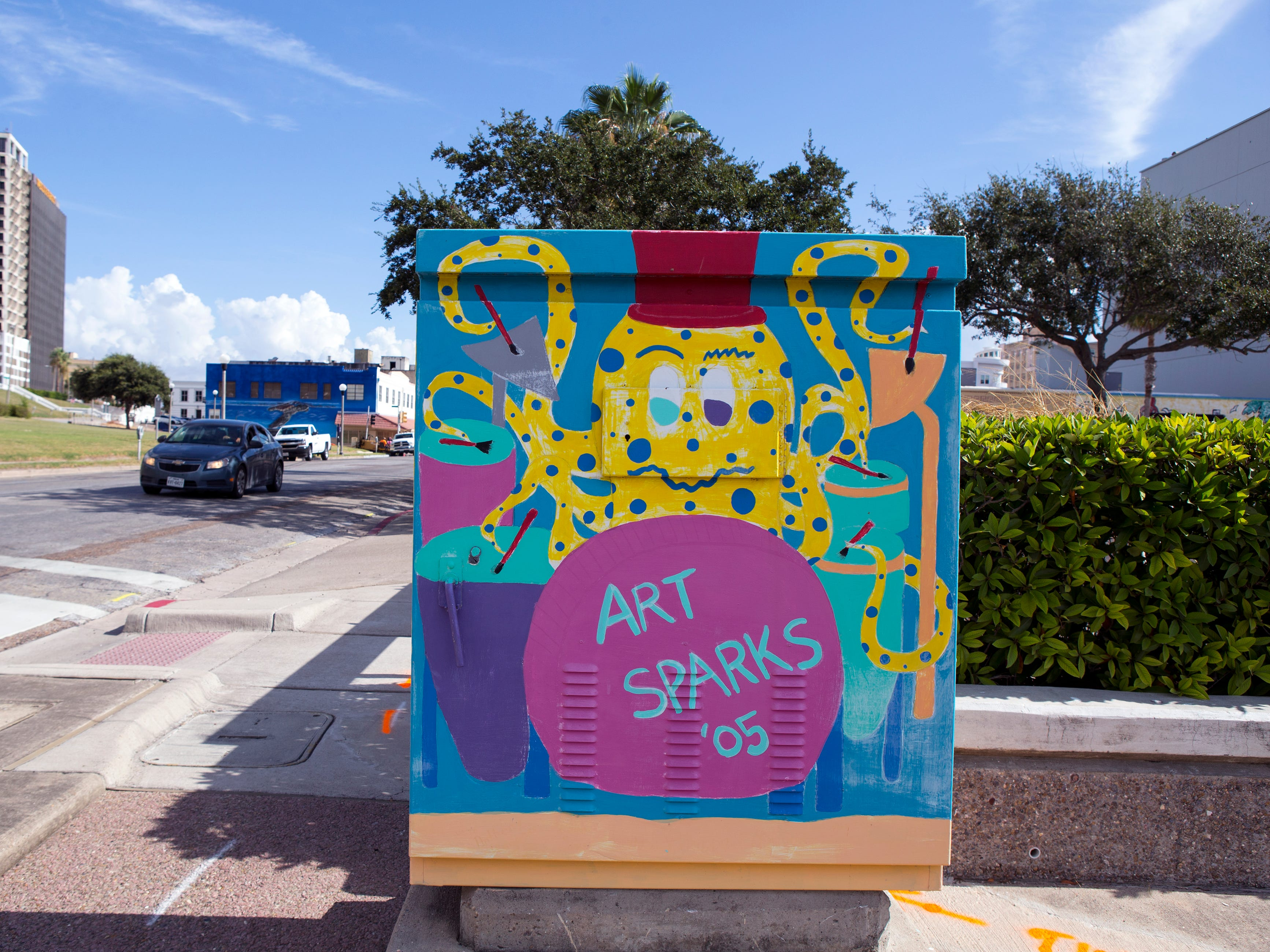 A painted utility box in downtown Corpus Christi is located near the corner of John Sartain and N. Mesquite streets. The Downtown Management District began the process of having the boxes painted in 1997 with a program called Art Sparks. The program allowed students interested in art to paint the boxes over the summer under the supervision of a teacher and get paid for their work. In 2004, the district began using commissioned artists.