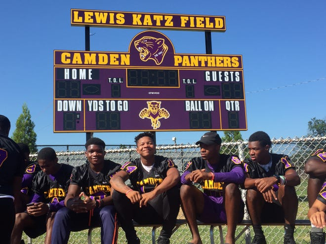 Members of the Camden High varsity football team gather in front of the new Farnham Park scoreboard. The Panthers' new field will be named in honor of Camden High alum Lewis Katz.