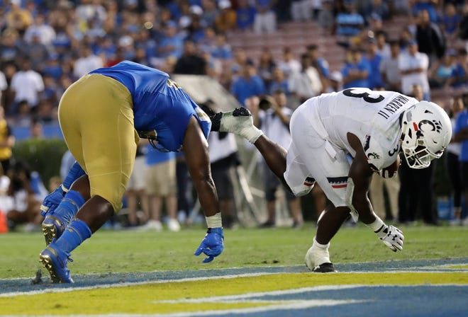 Cincinnati running back Michael Warren II, right, scores a rushing touchdown against UCLA during the fourth quarter of an NCAA college football game Saturday, Sept. 1, 2018, in Pasadena, Calif.
