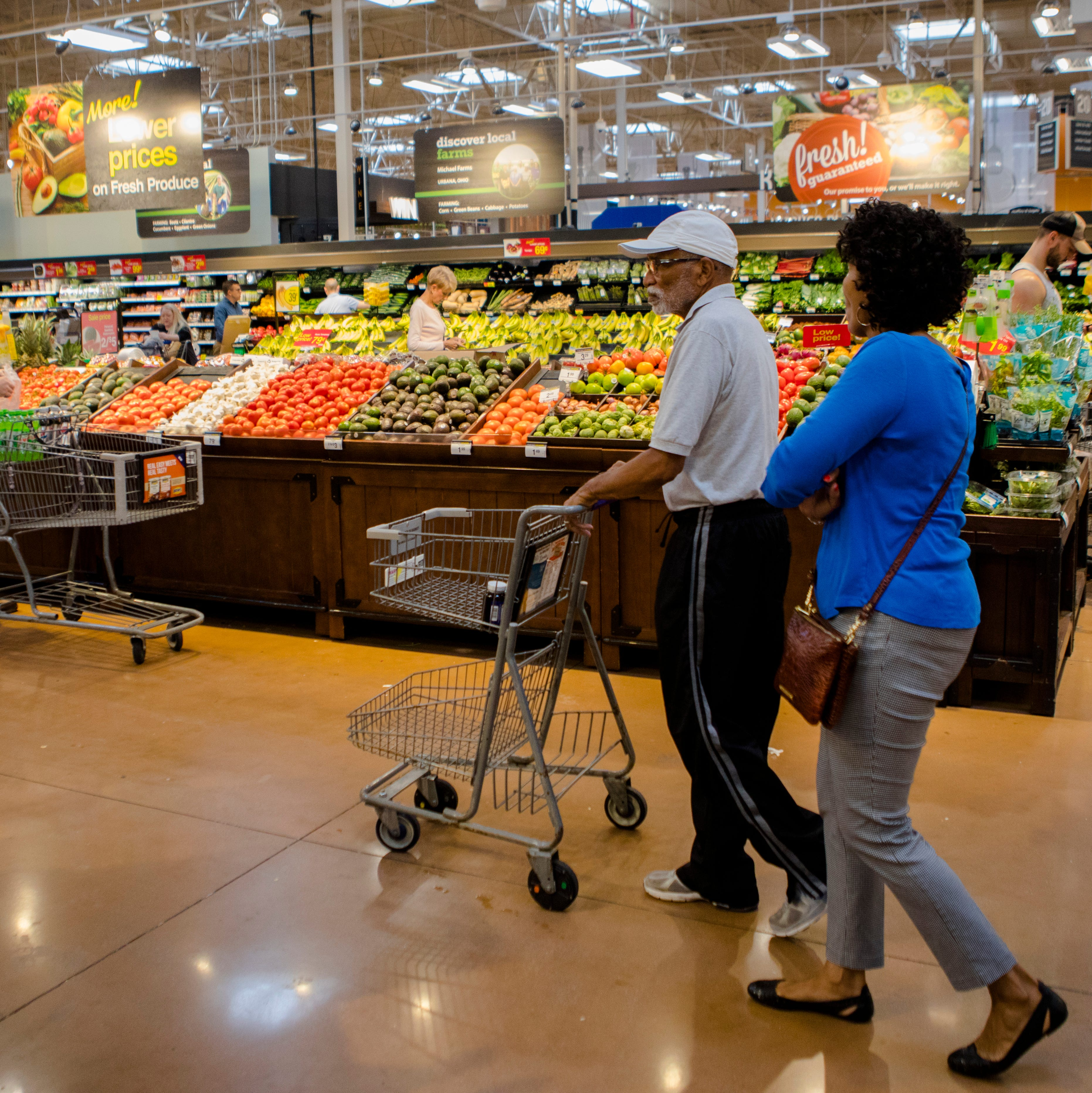 Shoppers walk through the produce section at...