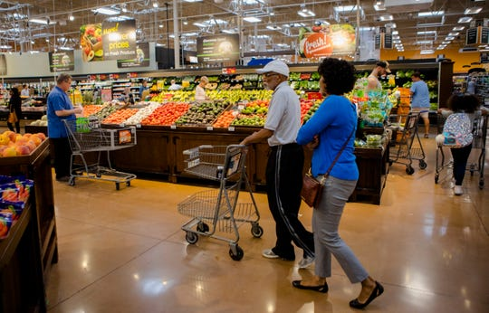 Shoppers walk through the produce section at Kroger in Oakley on Tuesday, Aug. 22, 2018.