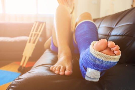 Broken Leg In A Plaster Cast With Soft Focus In The Background Over Light