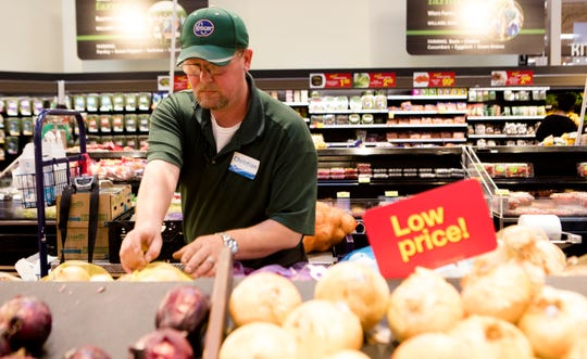 Christian Jones, a three year employee of Kroger, stock onions at Kroger in Oakley on Tuesday, Aug. 22, 2018.