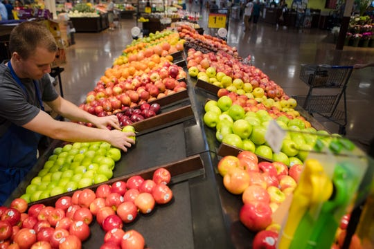 Kenny Vickroy, a four year employee of Krogers, stocks apples at Kroger in Oakley on Tuesday, Aug. 22, 2018.