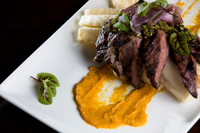Churrasco Con Chimi made with grilled outer skirt steak with house chimichurri, served atop a carrot puree with yucca fries tossed in garlic butter at Maize Arepas and Bar in Over-The-Rine on Aug. 24, 2018.