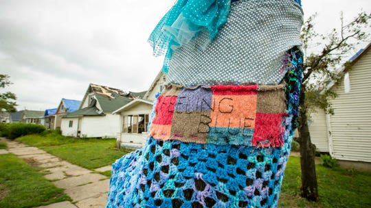 """An art installation 'yarn bomb' by local artist Linda Harvey of LeGrand, adorns a tornado-damaged tree in Marshalltown, Iowa, Monday, Aug. 20, 2018. """"We always focus on the negative but something as simple as the blue tree can be uplifting"""", Harvey said. With help from 20-25 volunteers so far, she is almost finished decorating a second tree near the damaged Lennox plant with more installations planned."""