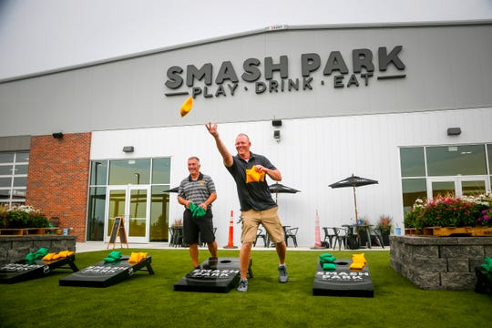 Mark Sullivan of Indianola Chad Parton of Bondurant play a game of bags at Smash Park in West Des Moines Aug. 14, 2018.
