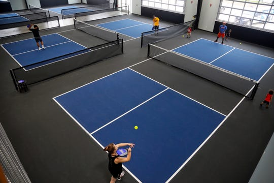 Guests play pickleball at Smash Park, an activity-based restaurant and bar that opens this week in West Des Moines.