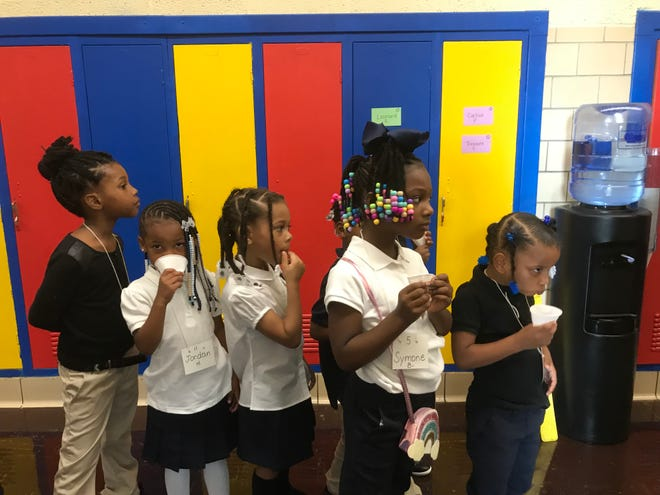Students at Gardner Elementary School in Detroit use white cups to sip water from one of the water coolers placed in the school.