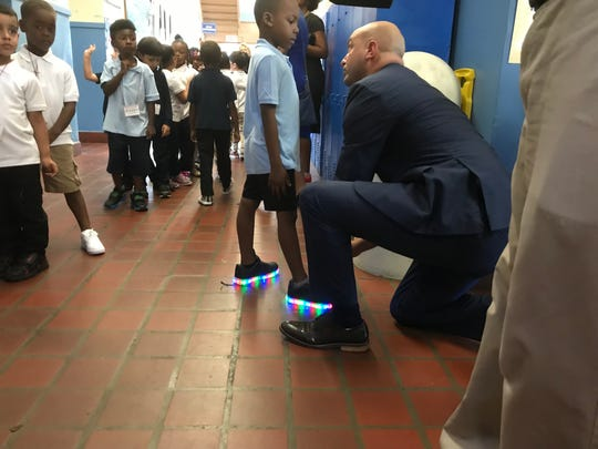 Detroit Superintendent Nikolai Vitti ties the shoes of a student passing through the hallway at Gardner Elementary School.