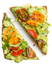 Slices of rye bread with avocado, colorful tomatoes and aragula leaves