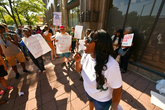 Joanna Underwood, an activist and mom of Detroit students at MacKenzie elementary, speaks to a crowd of dozens outside the Fisher Building, in Detroit on Tuesday. The crowd was gathered to protest the current water situation at Detroit public schools that has led to the students using bottled water.