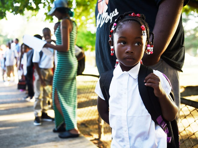 kindergartener Peyton Walters, 5, of Detroit waits in line with her parents for the start of school at Pasteur Elementary School.