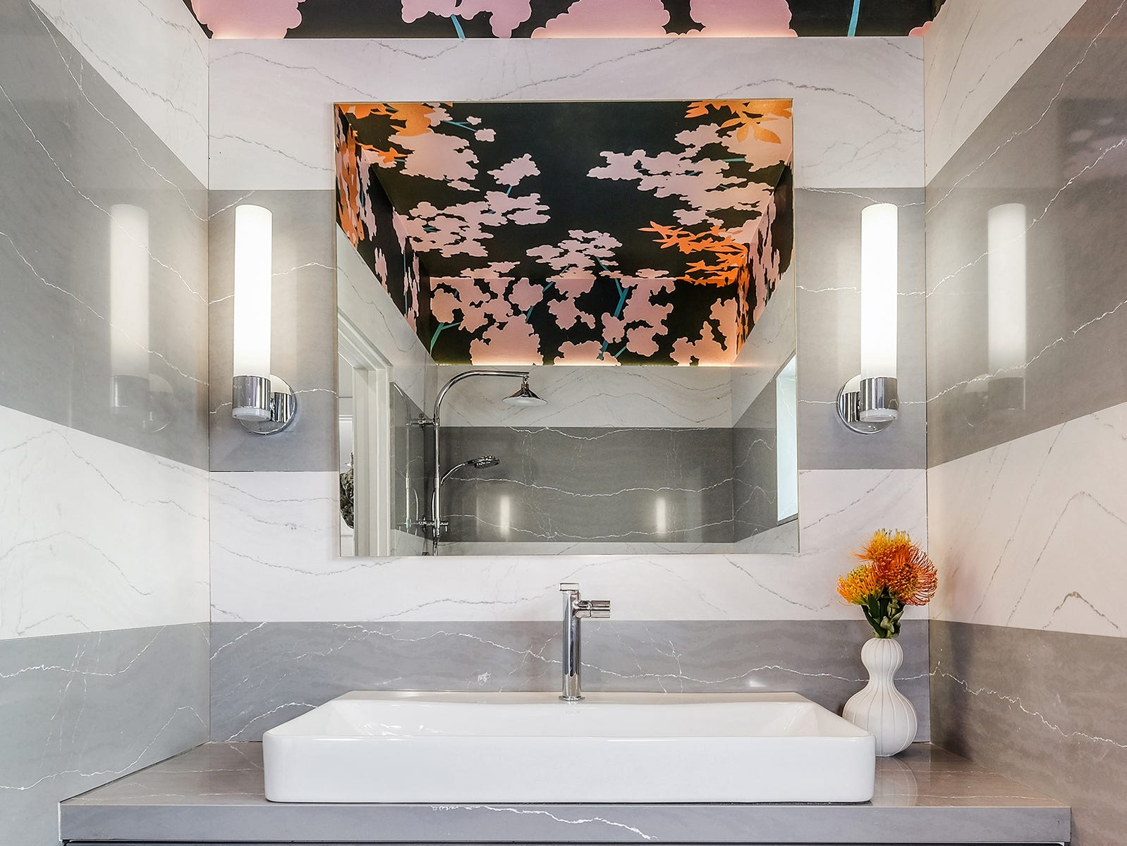 : A modern suspended vanity blends with gray and white stripes of stone, but it's the floral on a dark ground by Stephan Blachowski that pops on the ceiling.