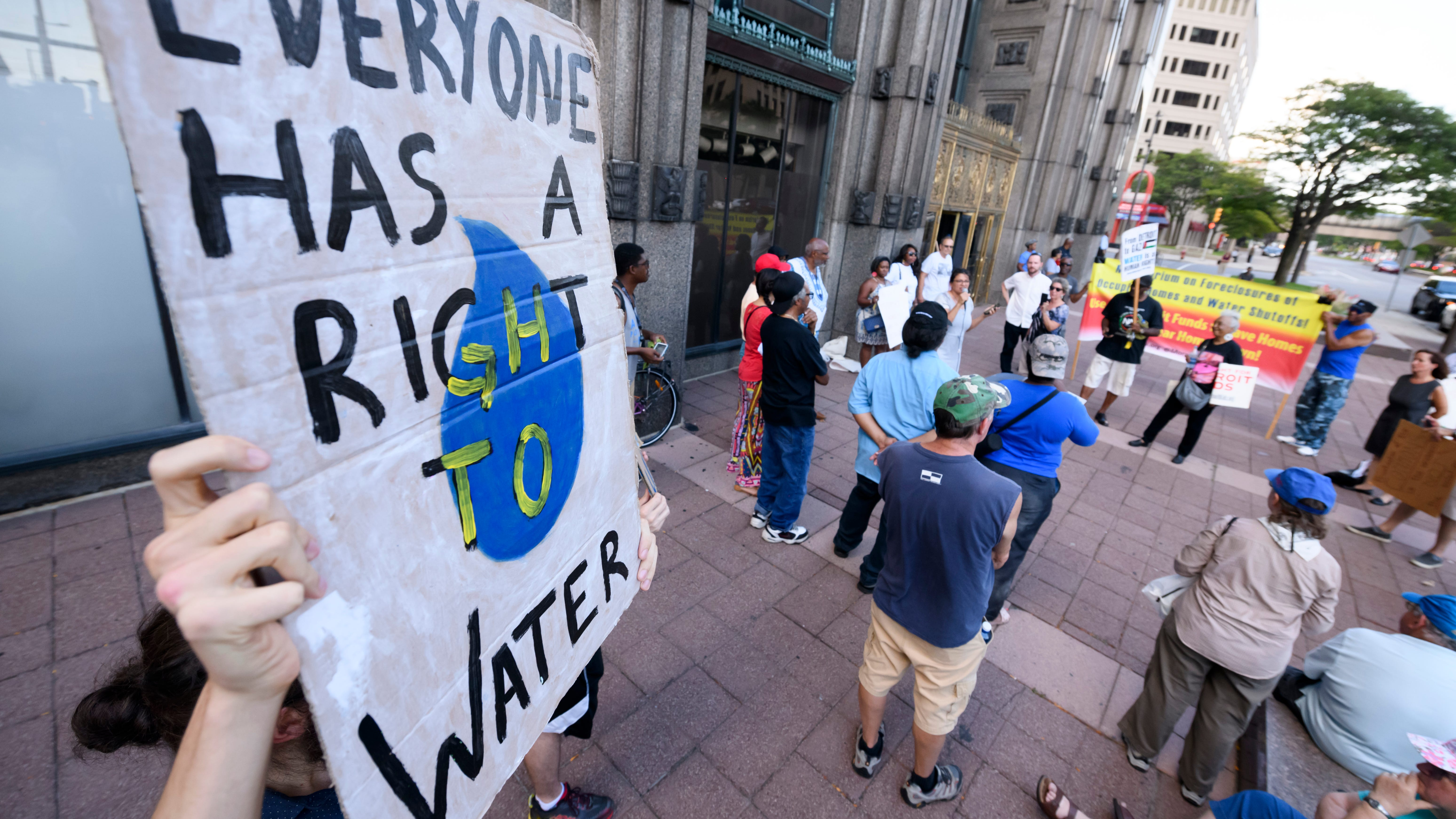 Signs are held during a demonstration and protest demanding safe and clean drinking water for students at Detroit Public Schools, held at the Fisher Building, home of the DPSCD administration office, in Detroit, September 4, 2018.