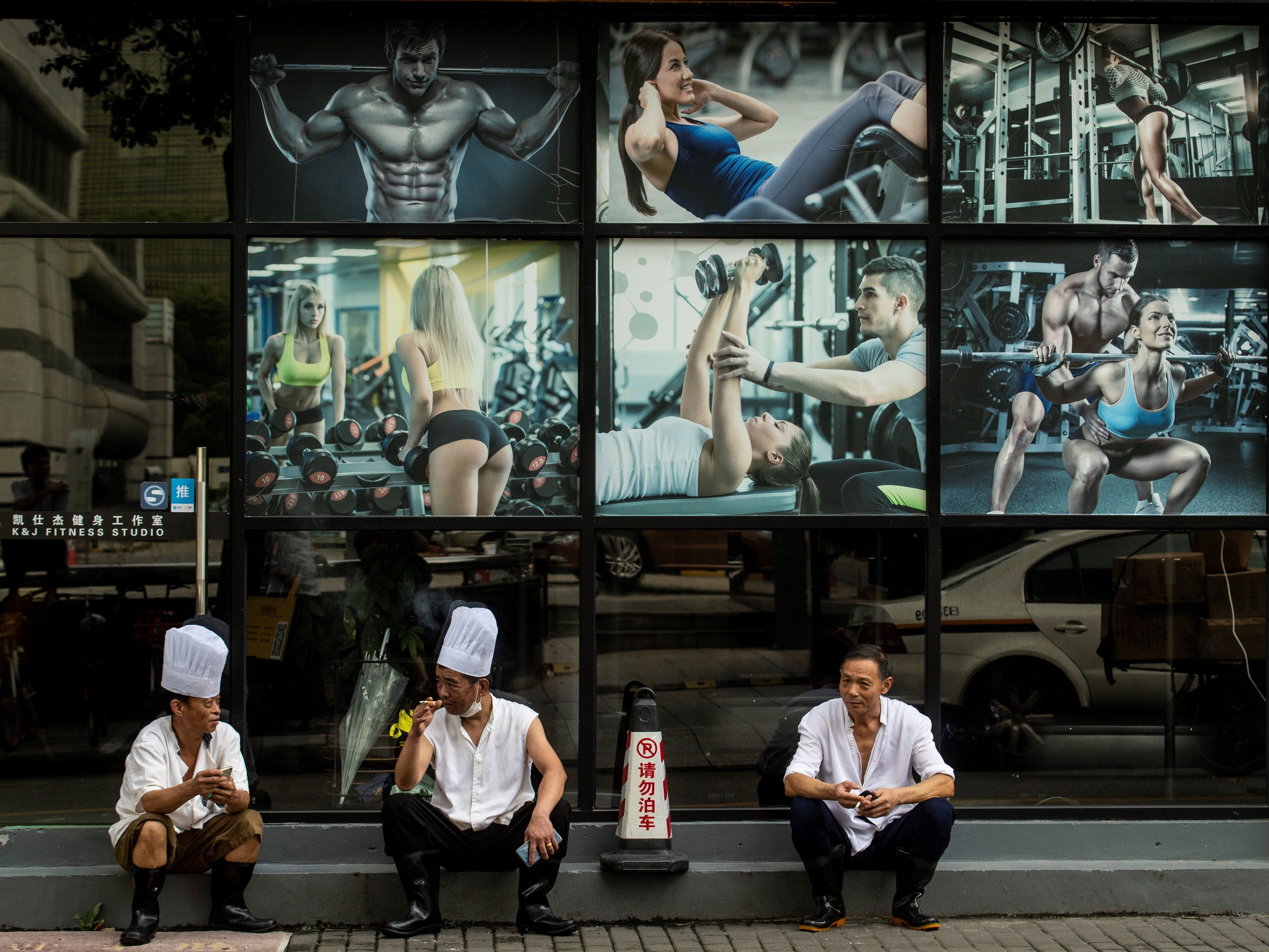 Three restaurant chefs take a break in front of a fitness studio in downtown Shanghai on September 4, 2018.